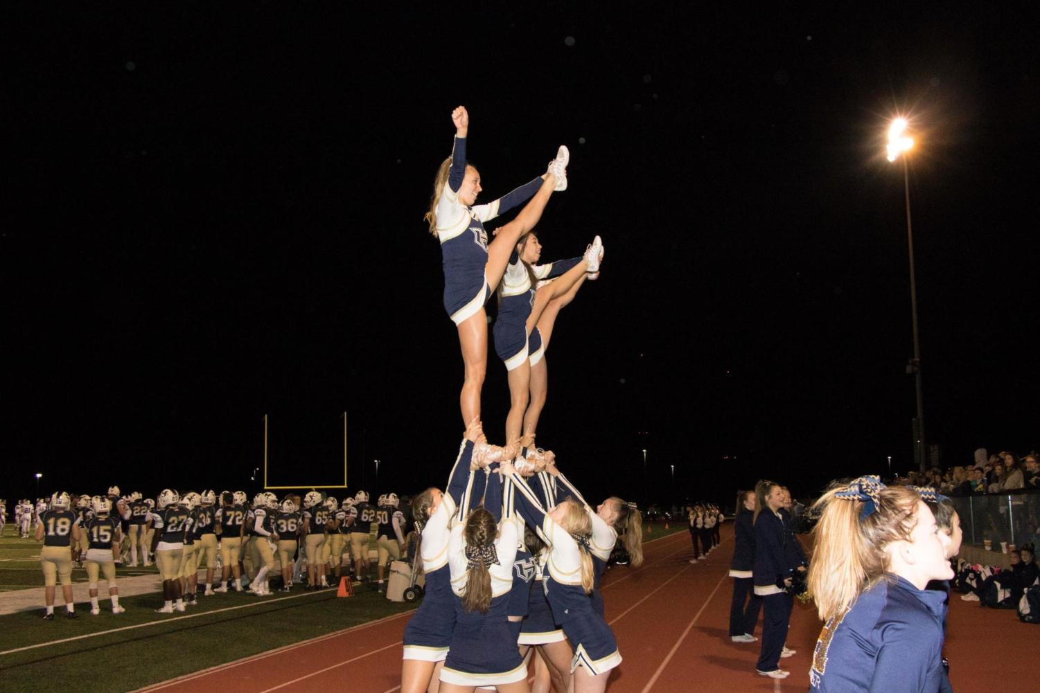 Holt Varsity Fall cheer hypes up the crowd with a heel stretch pyramid during half time.