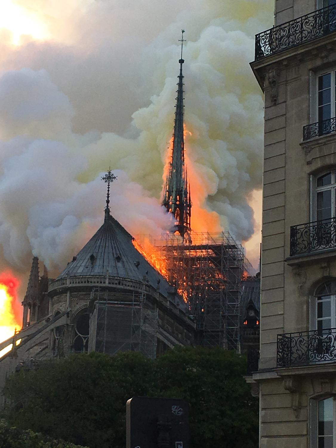 Tourists and French citizens alike watch in horror as a piece of their history burns in front of the.