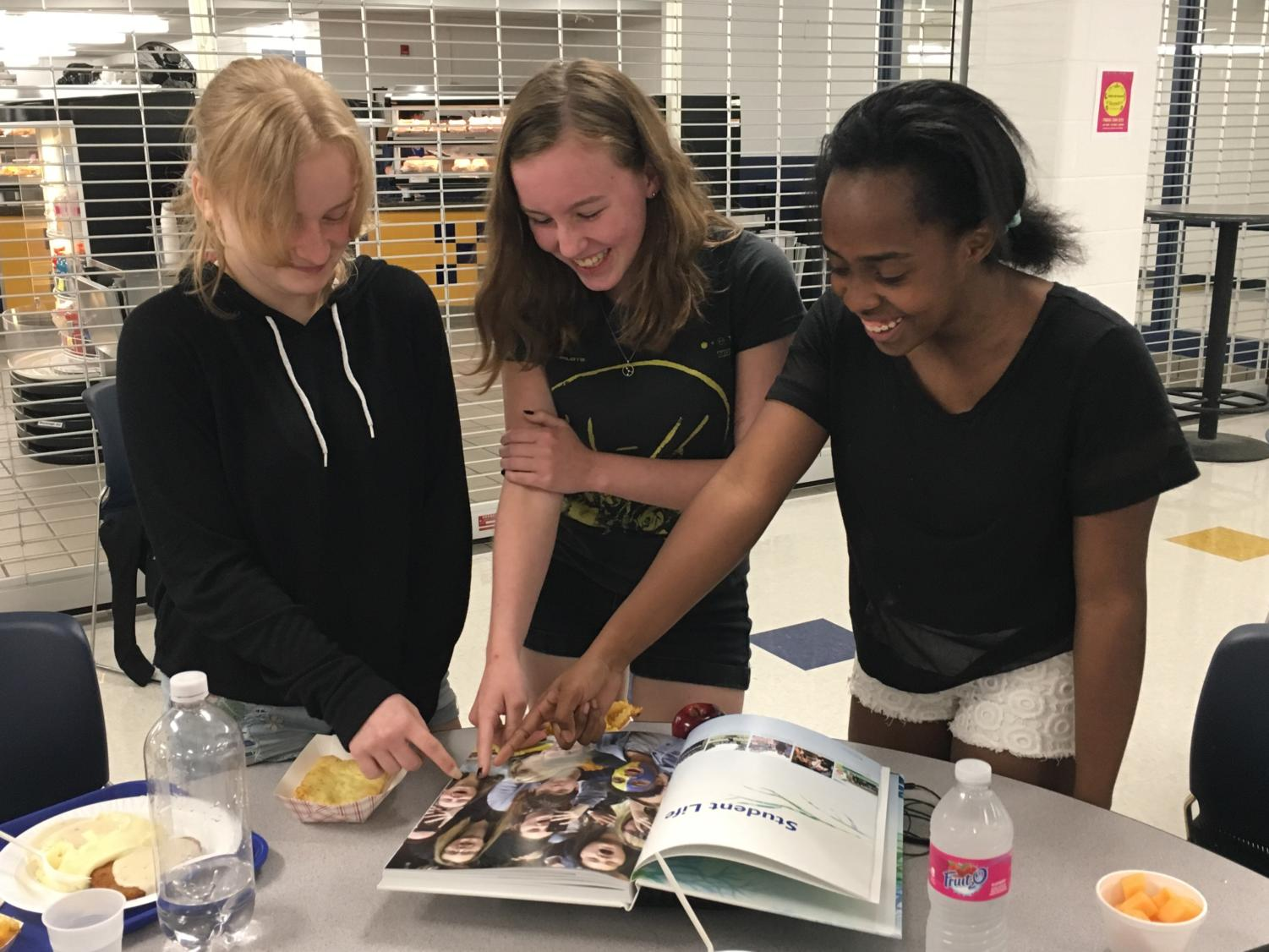 Three freshman, Alysa Hand, Kinslee Keatts and Natalie Sutherlin enjoy looking through the new yearbook.