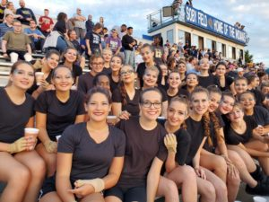 The Color Guard team , anxiously wanting to perform, waits patiently for halftime.