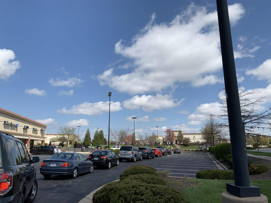 A+line+full+of+cars+at+Starbucks+wraps+around+the+building.%0A