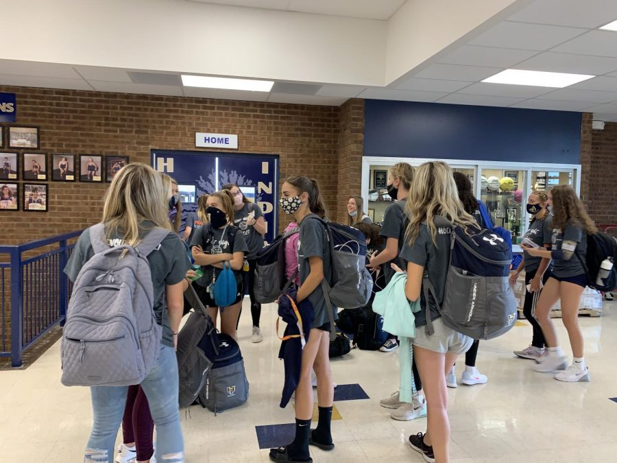 As the volleyball teams wait for their bus to take them to Francis Howell High School for an away game, they keep each other safe by wearing their masks.