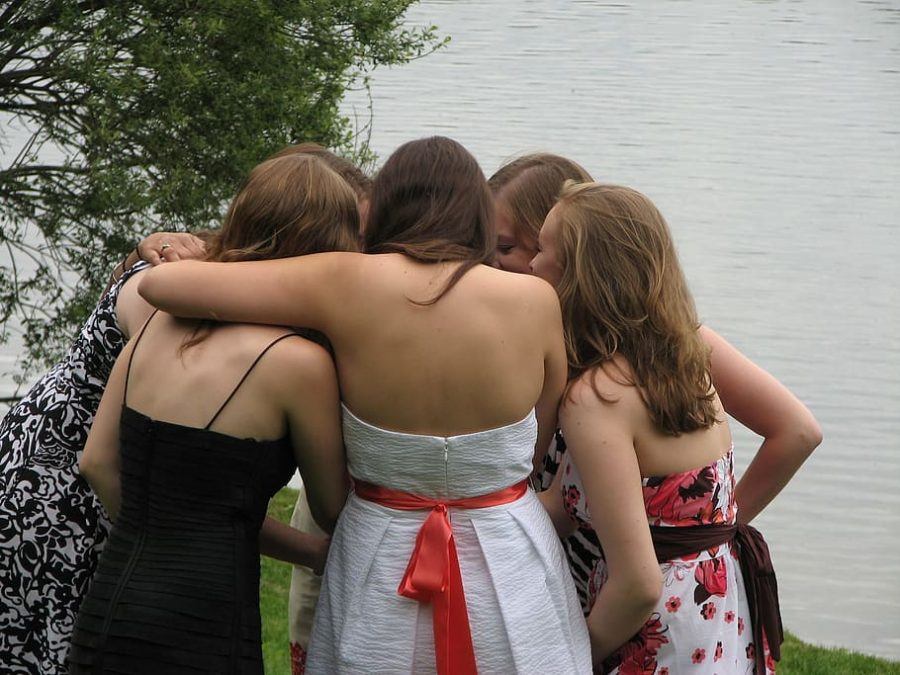 Girls are huddled together, hugging and hyping each other up for their school dance.
