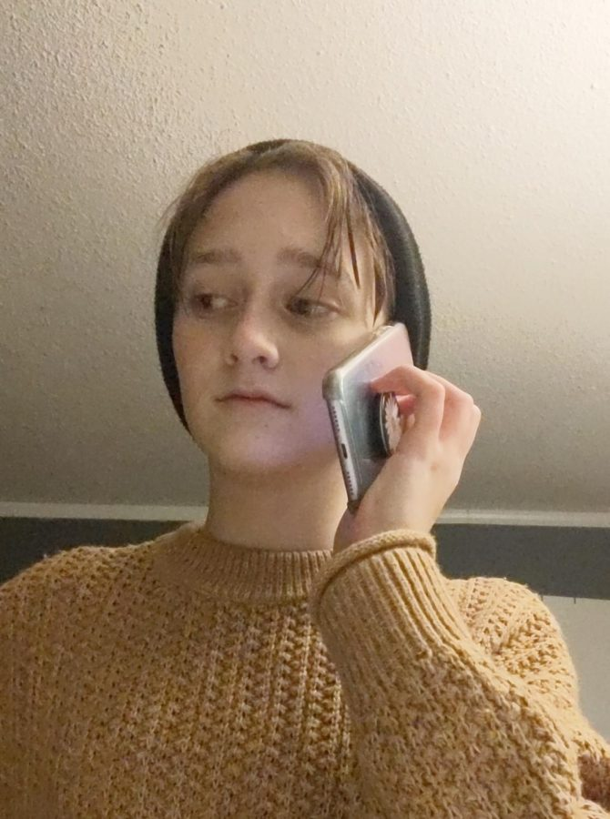 Student talks on the phone with a friend while stuck at home.