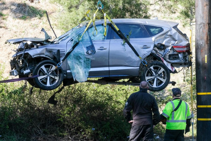 A crane is being used to lift up the SUV from a rollover accident in which belongs to Tiger Woods.
